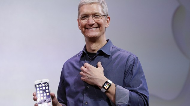 Tim Cook posing for photos with the iPhone 6 Plus and Apple Watch at the introduction launch event for both devices.