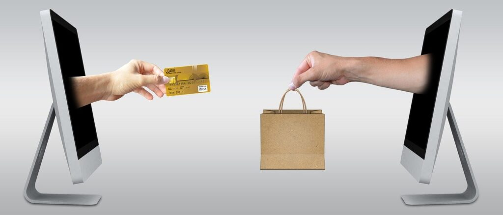 Two hands coming out of computers, one is holding a bag and the other is holding a credit card