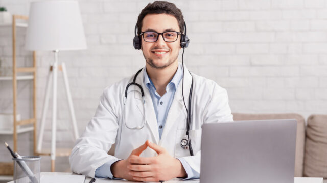 Health blog. Young doctor in headphones sitting at table with laptop